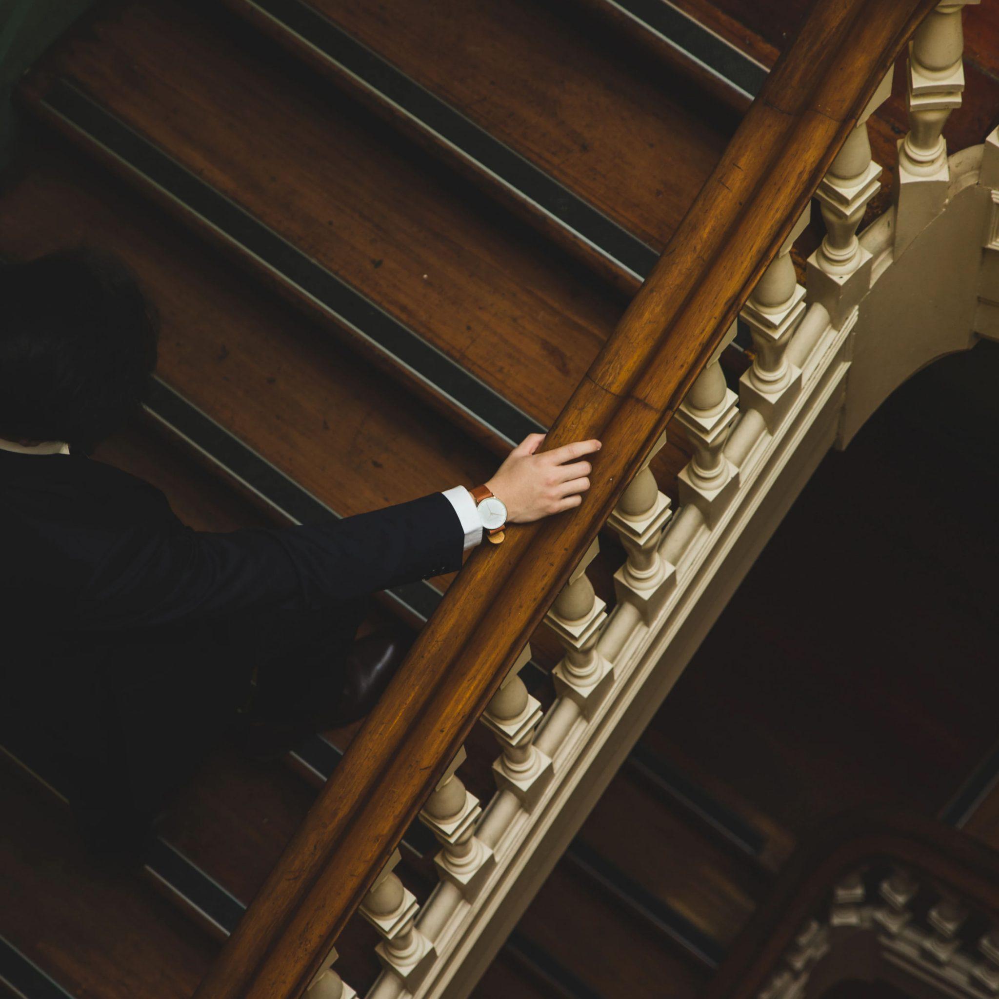 Un homme avec une belle montre monte des escaliers.
