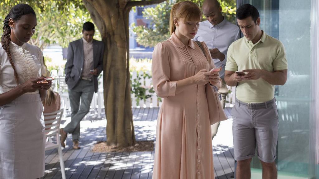 Image tirée de la série Black Mirror montrant des adultes, tous concentrés sur leur téléphone.